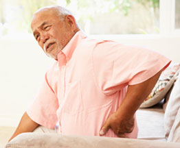 An elderly man holds his side in pain
